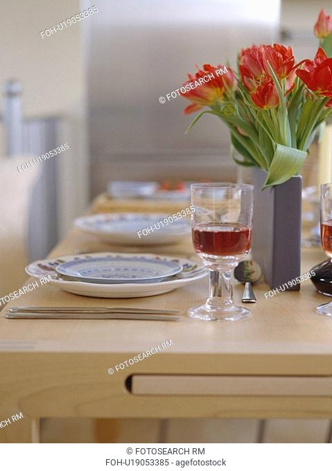 Close-up of red tulips in grey vase on pale wood table with place settings and glass of red wine