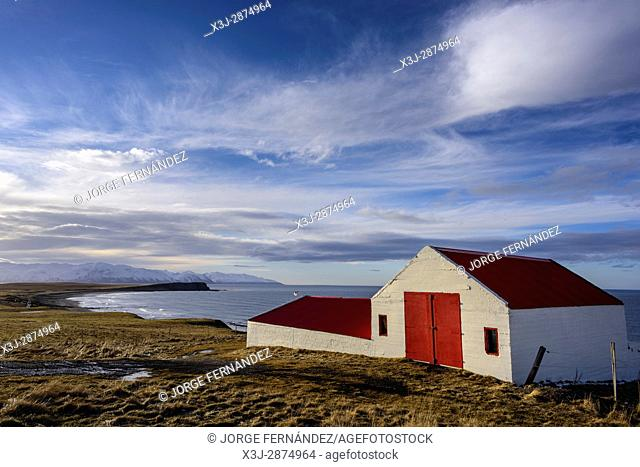 Colourful farm with red roof and door at sunset