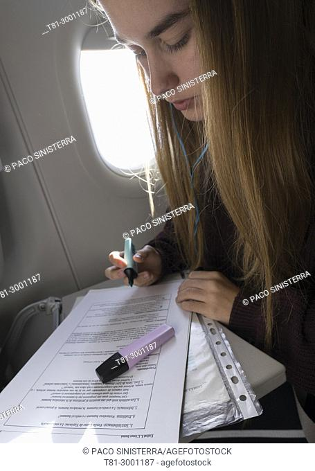 blonde girl doing work on the airplane
