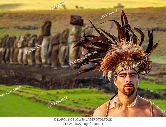 Native Rapa Nui man in tradititional costume and Moais in Ahu Tongariki, Rapa Nui National Park, Easter Island, Chile. MR