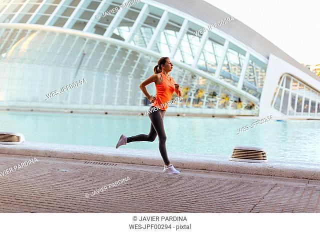 Spain, Valencia, woman running at Ciudad de las Artes y de Las Ciencias