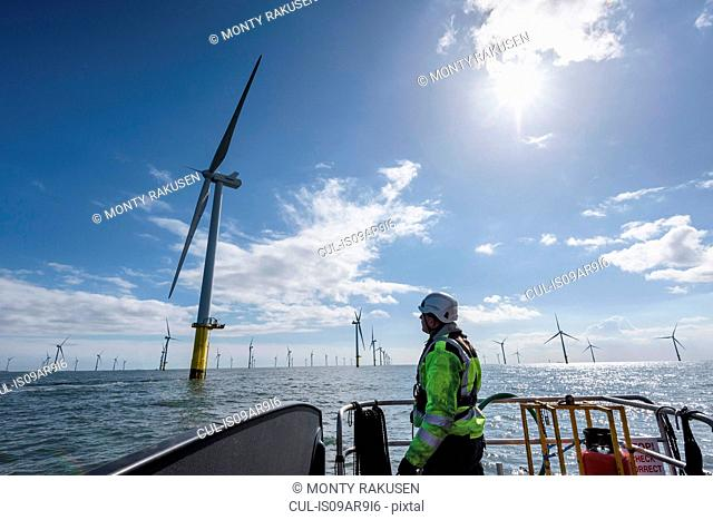 Worker looking out from ship to offshore wind farm
