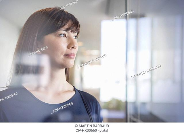 Pensive businesswoman looking out window