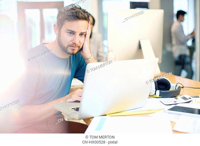 Serious creative businessman using laptop with head in hands in office