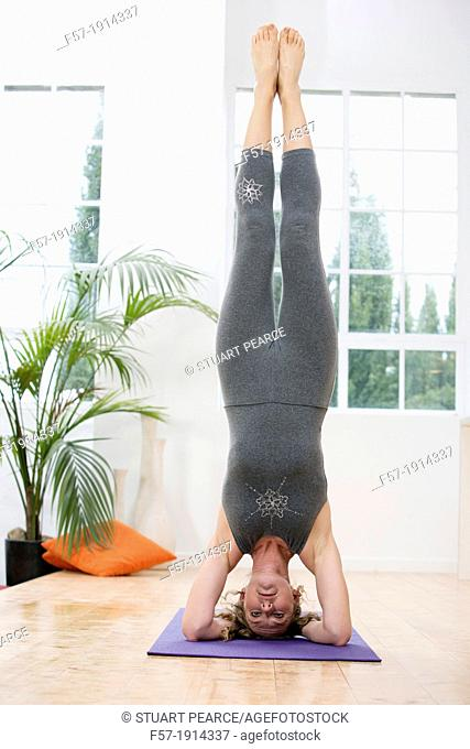 Healthy young woman doing the supported headstand yoga position