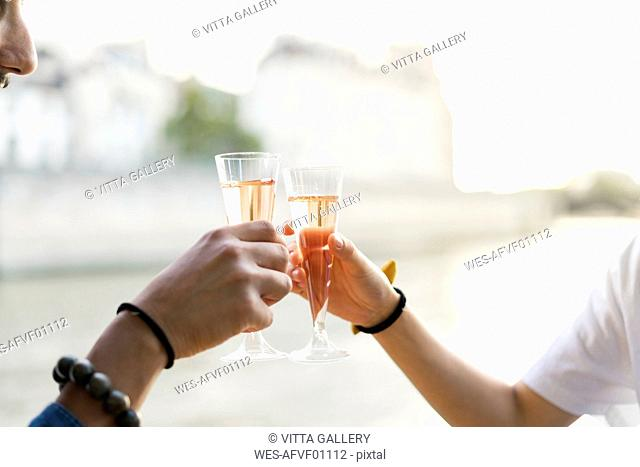 Close-up of couple clinking champagne glasses at the riverside