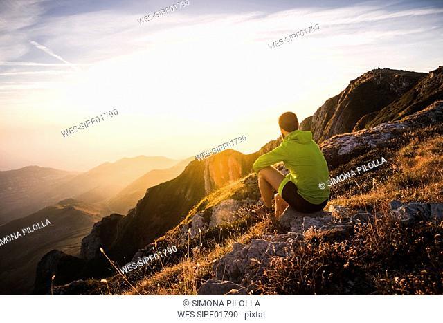 Italy, mountain running man sitting on rock looking at sunset
