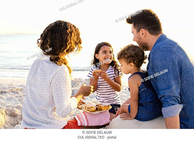 Couple with two girls having picnic on beach, Tuscany, Italy