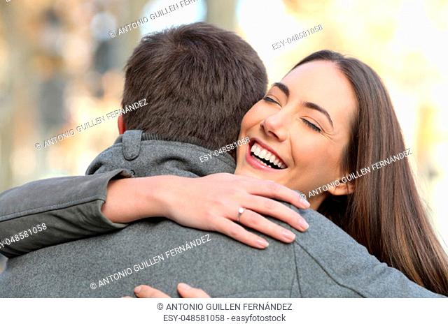 Portrait of a couple hugging after happy proposal in the street