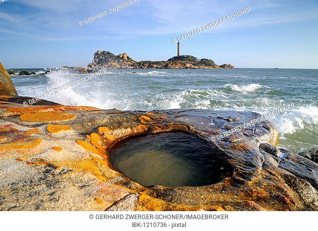 Surf and sandstone water basin in the bay of Ke Ga, in the back highest, 54m, and oldest, 1897, lighthouse, Vietnam, Asia