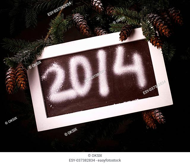 Chalkboard on the pine brach under the snow with 2014 new year