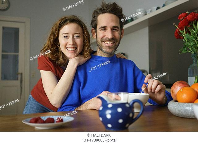 Portrait of smiling mid adult couple at table with breakfast in room