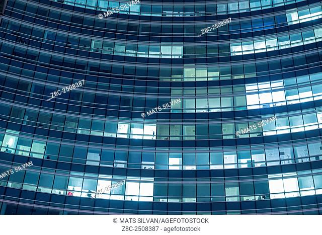 Modern office building with illuminated windows at night in Milan, Italy