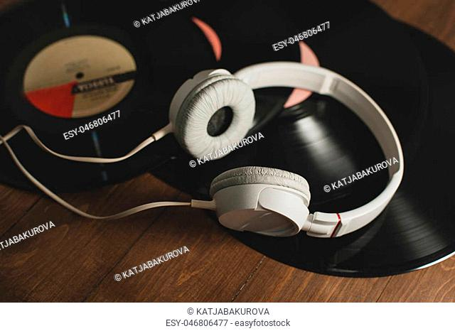 vinyl records on a wooden background and white headphones