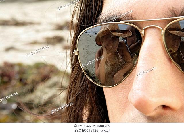 View of a womans reflection on a young mans sunglasses
