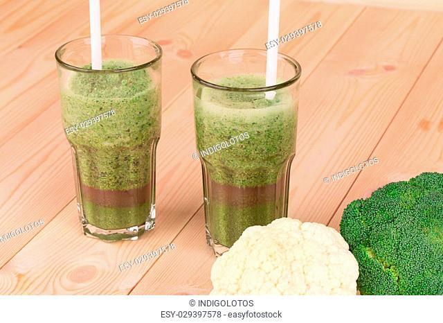 Close up of glass full of tasty kiwi juice. Wooden background
