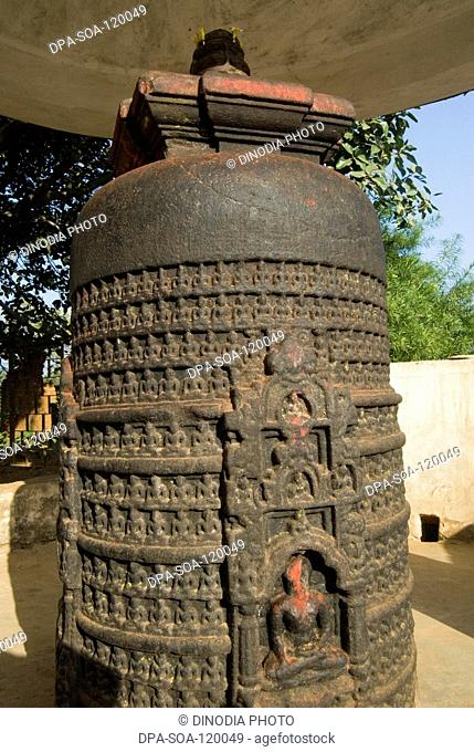 Seven feet high black marble column sculpted with 1008 figures of Buddha in meditation young pries anoints it with water; Itakhori; Jharkhand ; India