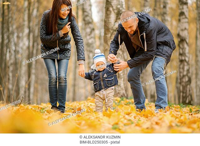 Middle Eastern parents walking with baby son in autumn