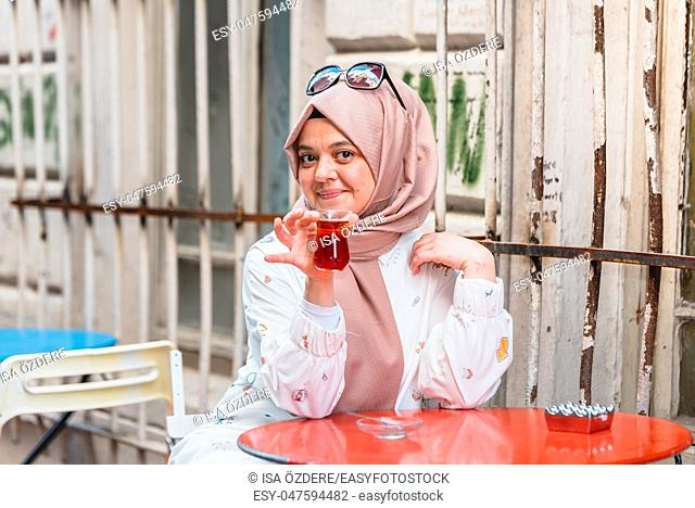 Beautiful Muslim woman in headscarf and fashionable modern clothes drinks Traditional Turkish drinks tea. Modern Muslim women lifestyle or travel tourist...