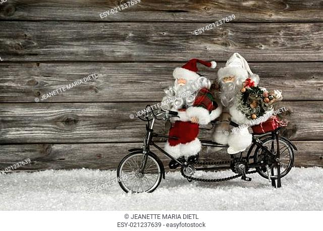 Funny wooden christmas background with two santa claus on a bicycle making xmas shopping