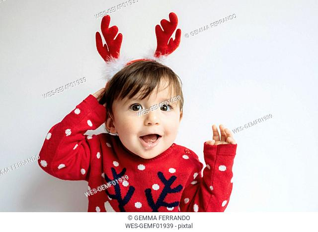 Portrait of baby girl with reindeer antlers headband at Christmas time