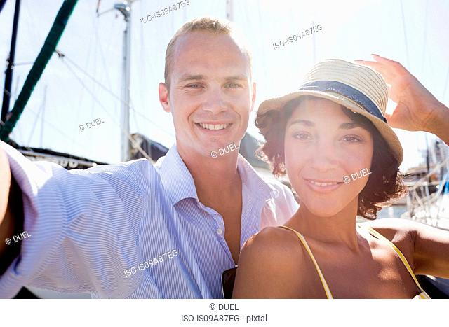 Young couple on yacht photographing themselves