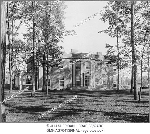 Photograph of a large two-story brick Roland Park in Baltimore, with a large front lawn and many trees hanging over the home, United States, 1920