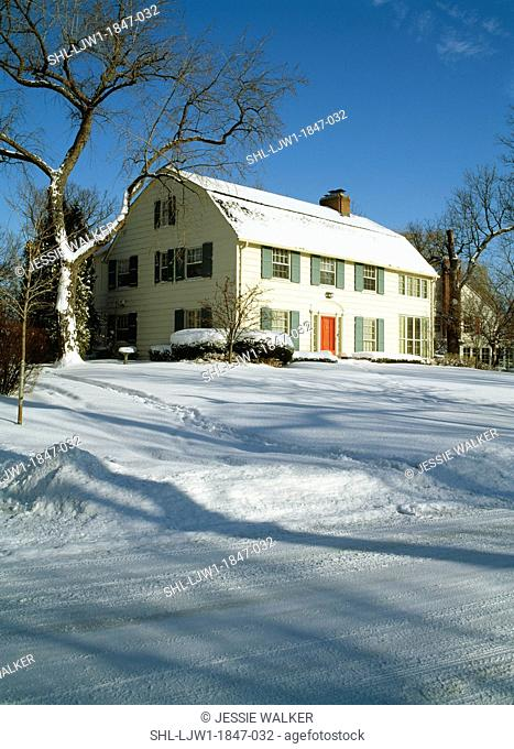 EXTERIORS: Two-story Colonial Revival home with window shutters, and bare trees in snow, vertical, blue sky, angle shot from street