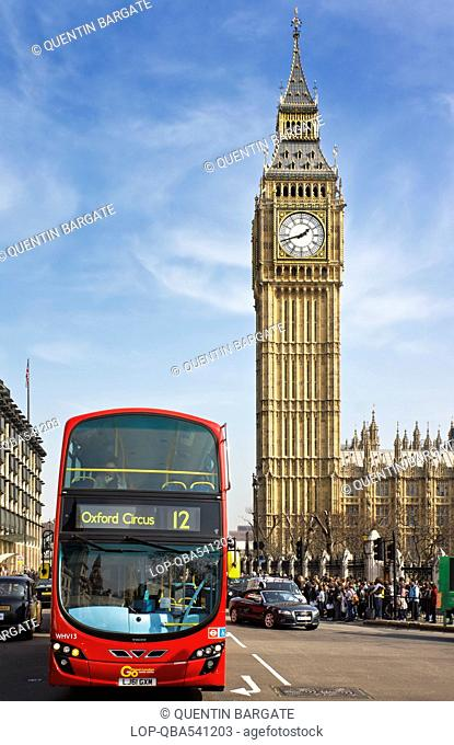 England, London, Westminster. A red London Bus opposite Big Ben, one of the most iconic landmarks in London