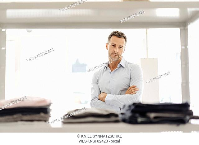 Portrait of confident businessman standing at shelf with clothes