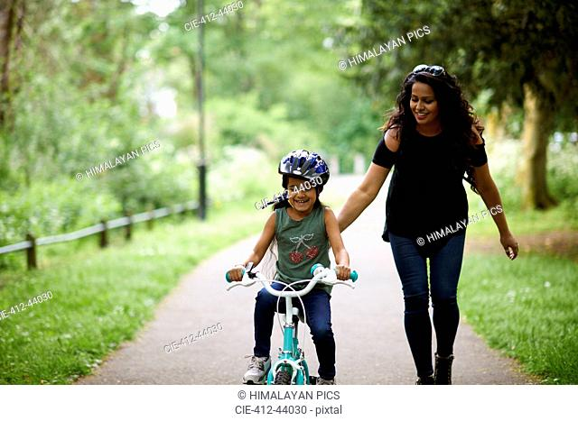 Happy mother teaching daughter how to ride bike