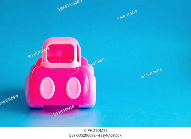 Children's toy plastic pink car on a blue background. Copy space