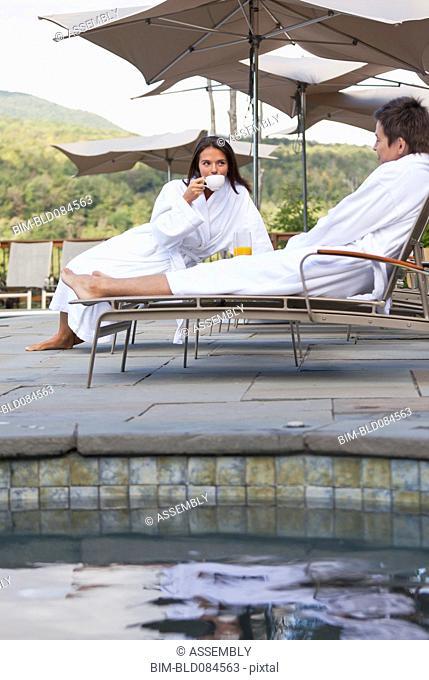 Couple enjoying breakfast near swimming pool