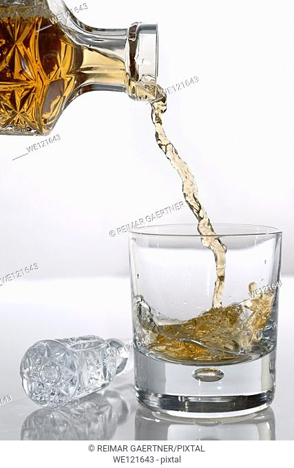 Pouring scotch from a crystal decanter into a wiskey tumbler glass on white background