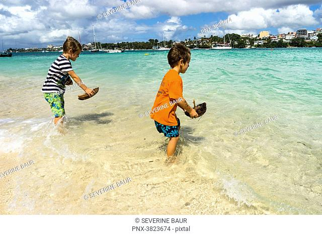 Two young boys, 5 and 7 years old, playing with small boat in coco ont he beach, Gosier island, Guadeloupe, France