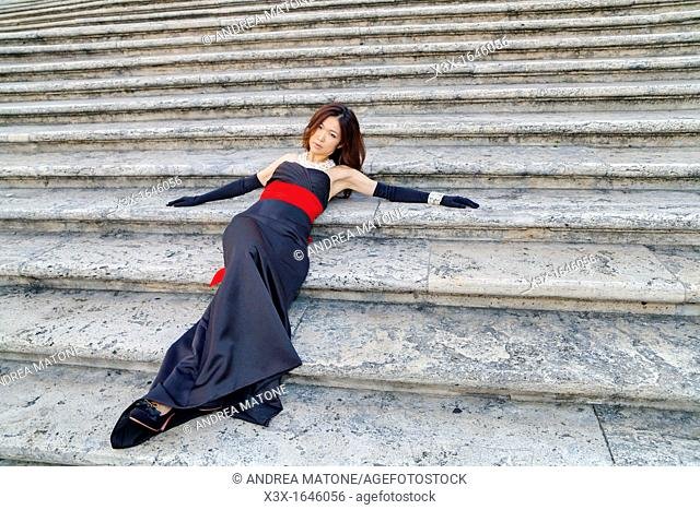 Asian girl laying on the stairs of Piazza di Spagna Rome Italy