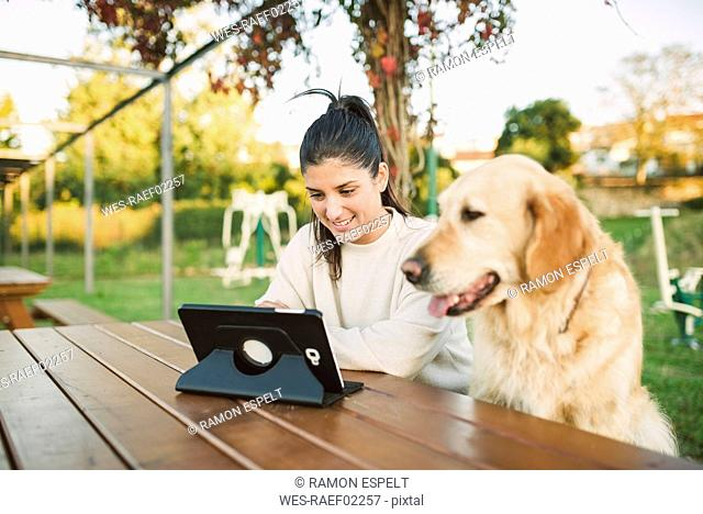 Smiling young woman using a tablet in a park with her dog