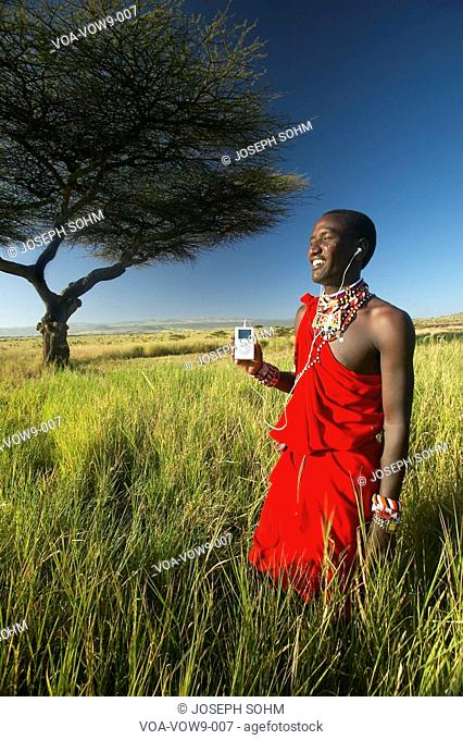 Masai Warrior near Acacia Tree listening to music on iPod by Apple in red surveying landscape of Lewa Conservancy, Kenya Africa