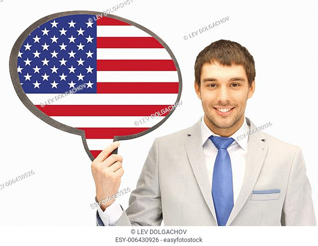 education, foreign language, english, people and communication concept - smiling young man or businessman in tie and suit holding text bubble of american flag