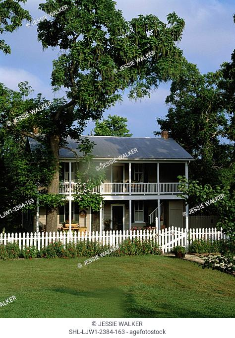 EXTERIORS: Two story home, white picket fence, porches on both levels run the length of the house, vertical