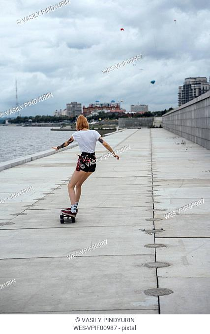 Rear view of young woman riding carver skateboard at the riverside