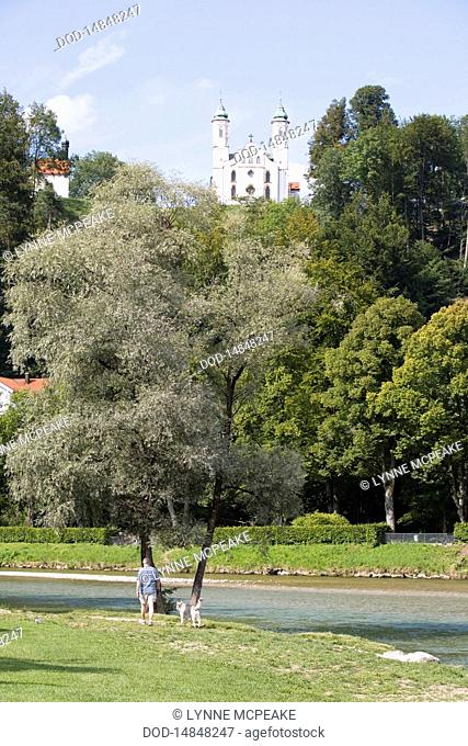 Germany, Bavaria, Wolfratshausen, Bad Toelz, man walking dog near River Isar with church in hill in background