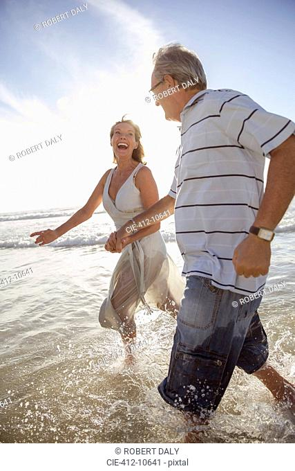Older couple playing in waves on beach