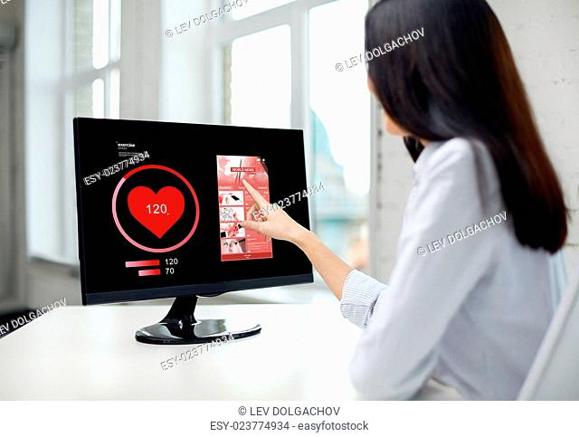 business, people, technology and healthcare concept - close up of woman with heart pulse icon and news web page on computer monitor in office