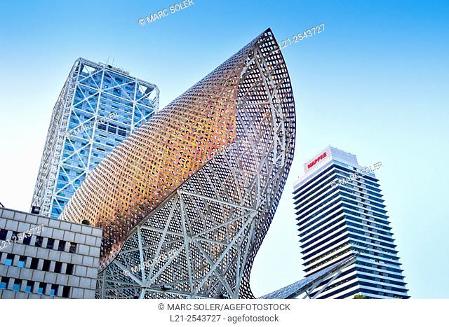 Frank O. Gehry's Golden Fish Sculpture, Hotel Arts and Mapfre Tower in background. Port Olimpic, Vila Olimpica, Barcelona, Catalonia, Spain