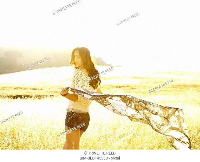 Carefree woman with outstretched arms holding a flowing scarf blowing in the wind walking in nature looking back at camera