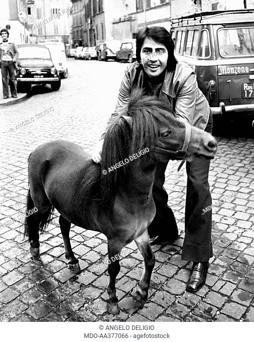 Lando Fiorini with a pony. Italian singer and actor Lando Fiorini (Leopoldo Fiorini) stroking a pony. Rome, 1970s
