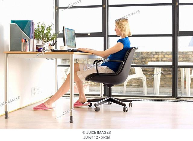Woman using computer at desk in home office by window, side view