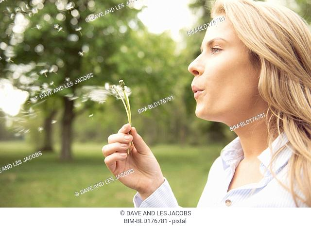 Caucasian woman blowing dandelion seeds