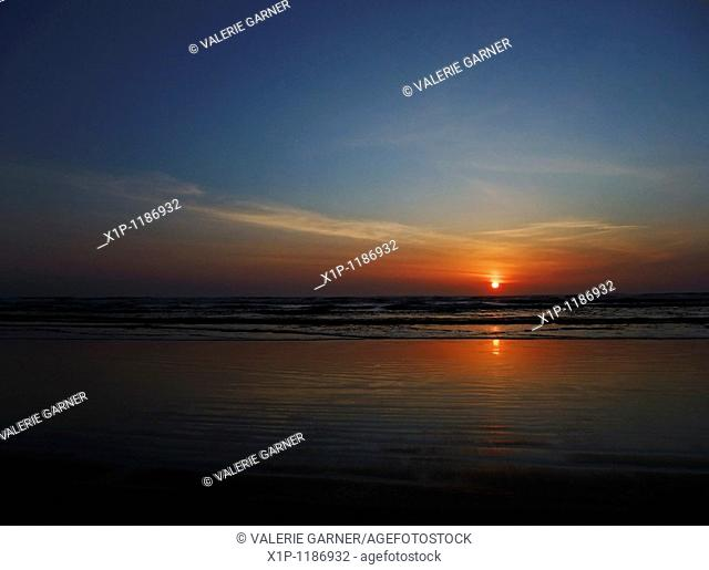 This stock photo is a stunning sunset at the beach as the sun is just about to dip over the horizon Horizontal format this conveys of concepts of vacation